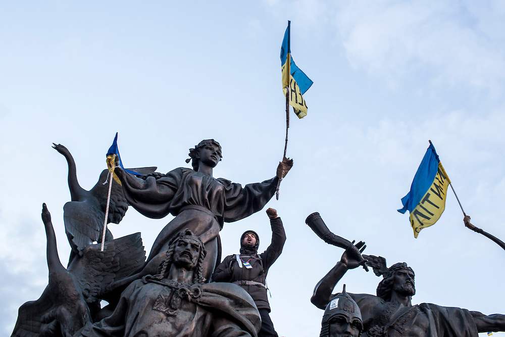 KIEV, UKRAINE - DECEMBER 6: An anti-government protester shouts from  a statue on December 6, 2013 in Kiev, Ukraine. Thousands of people have been protesting against the government since a decision by Ukrainian president Viktor Yanukovych to suspend a trade and partnership agreement with the European Union in favor of incentives from Russia. (Photo by Brendan Hoffman/Getty Images) *** Local Caption ***