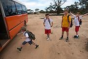 Left to Right, Harrison McNee, Benjamin McNee, Matthew Haggerty and Declan McNee board the bus that will take them to school in Wyalkatchem. Western Australian Wheatbelt. 10 December 2012 - Photograph by David Dare Parker