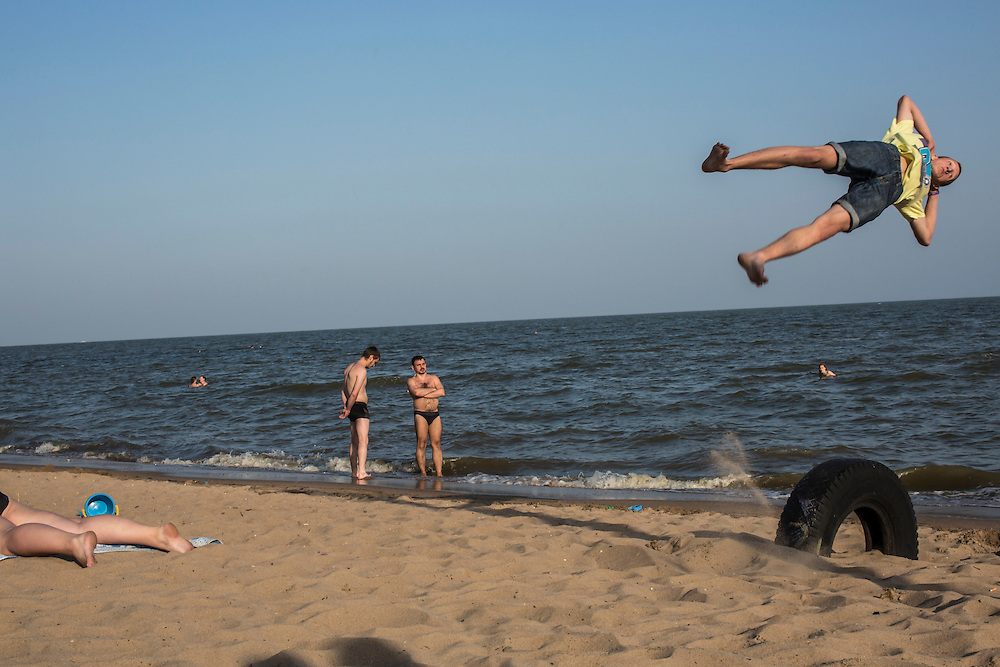 MARIUPOL, UKRAINE - MAY 18: Men practice parkour on the beach on May 18, 2014 in Mariupol, Ukraine. A week before presidential elections are scheduled, questions remain whether the eastern regions of Donetsk and Luhansk are stable enough to administer the vote. (Photo by Brendan Hoffman/Getty Images) *** Local Caption ***