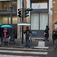 People wait at a crosswalk on a rainy day in Rome, Italy