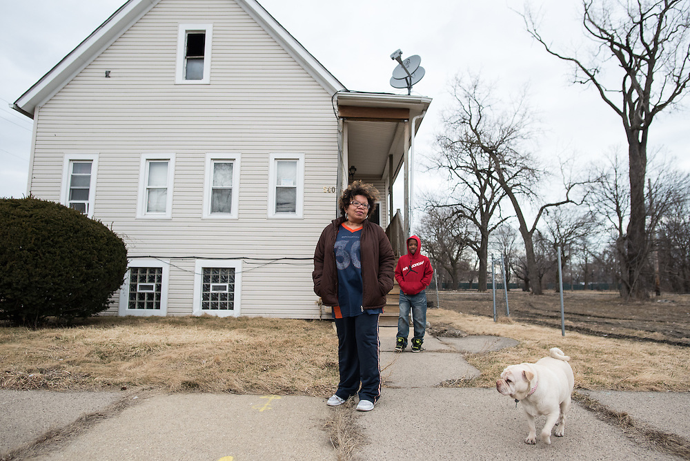 Margaret and one of her grandson's Malik and dog Roxie in front of the family house in Englewood which they are in danger of losing to Norfolk Southern.