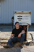 man sitting by an abandoned gas pump in rural South Carolina