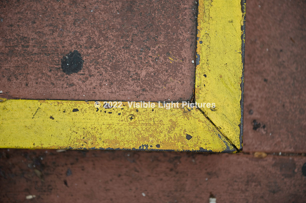 Yellow painted metal edge on a brown sidewalk step.
