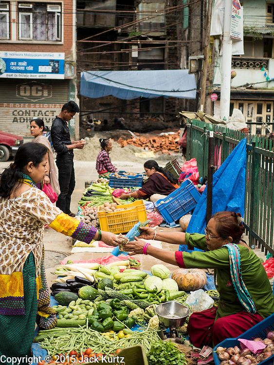 06 AUGUST 2015 - KATHMANDU, NEPAL: A produce market in central Kathmandu with a home destroyed in the earthquake in the background. The Nepal Earthquake on April 25, 2015, (also known as the Gorkha earthquake) killed more than 9,000 people and injured more than 23,000. It had a magnitude of 7.8. The epicenter was east of the district of Lamjung, and its hypocenter was at a depth of approximately 15 km (9.3 mi). It was the worst natural disaster to strike Nepal since the 1934 Nepal–Bihar earthquake. The earthquake triggered an avalanche on Mount Everest, killing at least 19. The earthquake also set off an avalanche in the Langtang valley, where 250 people were reported missing. Hundreds of thousands of people were made homeless with entire villages flattened across many districts of the country. Centuries-old buildings were destroyed at UNESCO World Heritage sites in the Kathmandu Valley, including some at the Kathmandu Durbar Square, the Patan Durbar Squar, the Bhaktapur Durbar Square, the Changu Narayan Temple and the Swayambhunath Stupa. Geophysicists and other experts had warned for decades that Nepal was vulnerable to a deadly earthquake, particularly because of its geology, urbanization, and architecture.      PHOTO BY JACK KURTZ