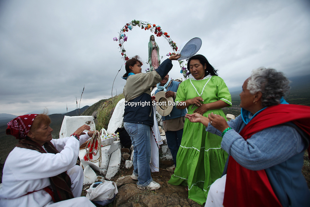 Followers of Nino Fidencio help dress a faith healer at a prayer and healing session on top of a hill just outside of Espinazo, Mexico on October 17, 2009. Followers of Nino Fidencio believe that his spirit can posses other healers, who once possessed speak in a child like voice and perform a variety of medical cures on their followers. His believers, an estimated 20,000, gather in his hometown for a three-day festival twice a year in March and October. (Photo/Scott Dalton).