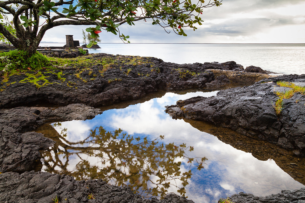 On the horizon one can see the very long seawall that protects Hilo, Coconut Island, and Hilo Bay. In the foreground skyward reflections bounce from the lagoons of Coconut Island.