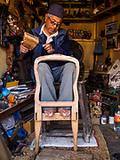 15 MARCH 2017 - BUNGAMATI, NEPAL:  A woodcarver in Bungamati works on a chair. Bungamati, a community of wood carvers and artisans, used to be a stop on the tourist trail of the Kathmandu valley but since the 2015 earthquake few tourists visit the community. Recovery seems to have barely begun nearly two years after the earthquake of 25 April 2015 that devastated Nepal. In some villages in the Kathmandu valley workers are working by hand to remove ruble and dig out destroyed buildings. About 9,000 people were killed and another 22,000 injured by the earthquake. The epicenter of the earthquake was east of the Gorka district.            PHOTO BY JACK KURTZ