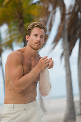 sexy man on the beach with sand in his hands