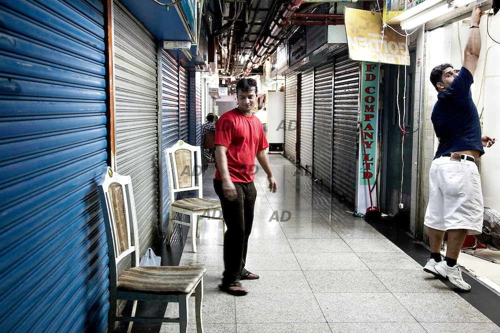 Restaurant closing time. *** General Caption *** Chungking Mansions building, located at 36-44 Nathan Road in Tsim Sha Tsui, is supposedly residential, it is made up of a labyrinth of hundreds  low cost guesthouses, curry restaurants, African bistros, clothing shops, sari stores, and foreign exchange offices. It often acts as a large gathering place for some of the ethnic minorities in Hong Kong, particularly South Asians (Indians, Nepalese, Pakistanis, Bangladeshis and Sri Lankans), Middle Eastern people, Nigerians, Europeans, Americans, and many other peoples of the world. Chungking Mansions is 17 stories tall and consists of five blocks, A, B, C, D and E. There are two lifts in each block, one of which serves even-numbered floors, the other one odd-numbered floors. A CCTV camera system exists at the ground floor level for each of the lift cars. The first two floors are however common space where you can wander around under the blocks , the third floor is actually a terrace level between the blocks where the tower blocks rise out of the base of the building and all floors above this are accessible only by the stairways and lifts contained in each block. It is also known to be a centre of drugs, and a refuge for petty criminals, scammers, and illegal immigrants. 208 CCTVs were installed throughout the building in 2004 and under the central control of a security company. It also hires security guards and cleaning workers to patrol in the building day to night and ensure the cleanliness of the building respectively. From time to time, police officers and the immigration officers check the identity of the people inside this building in order to crackdown on drug-trafficking, overstaying and other criminal offences. With all these effort the security and environment in Chungking Mansions has been improving significantly.
