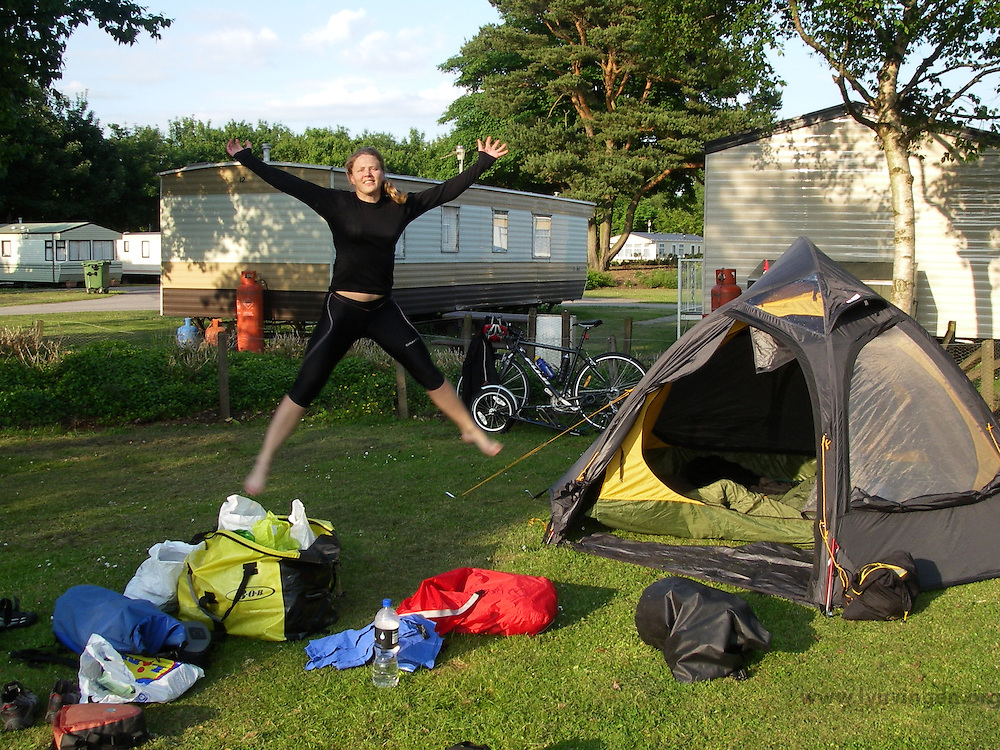 Girl jumping by tent..........