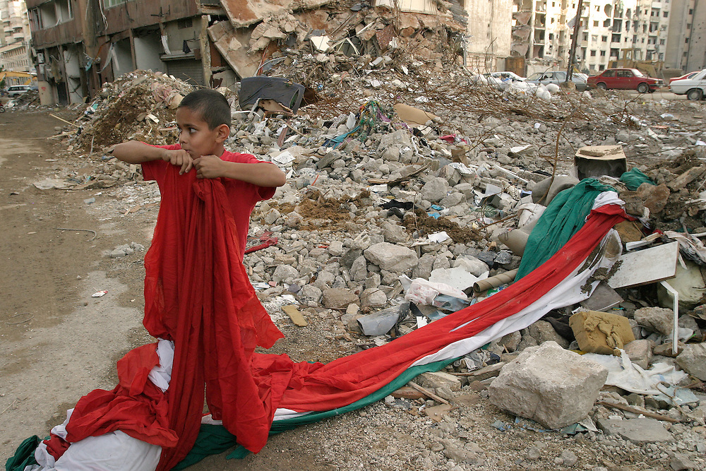 A boy tears fabric from a giant Lebanese flag in the ruins of an apartment building 