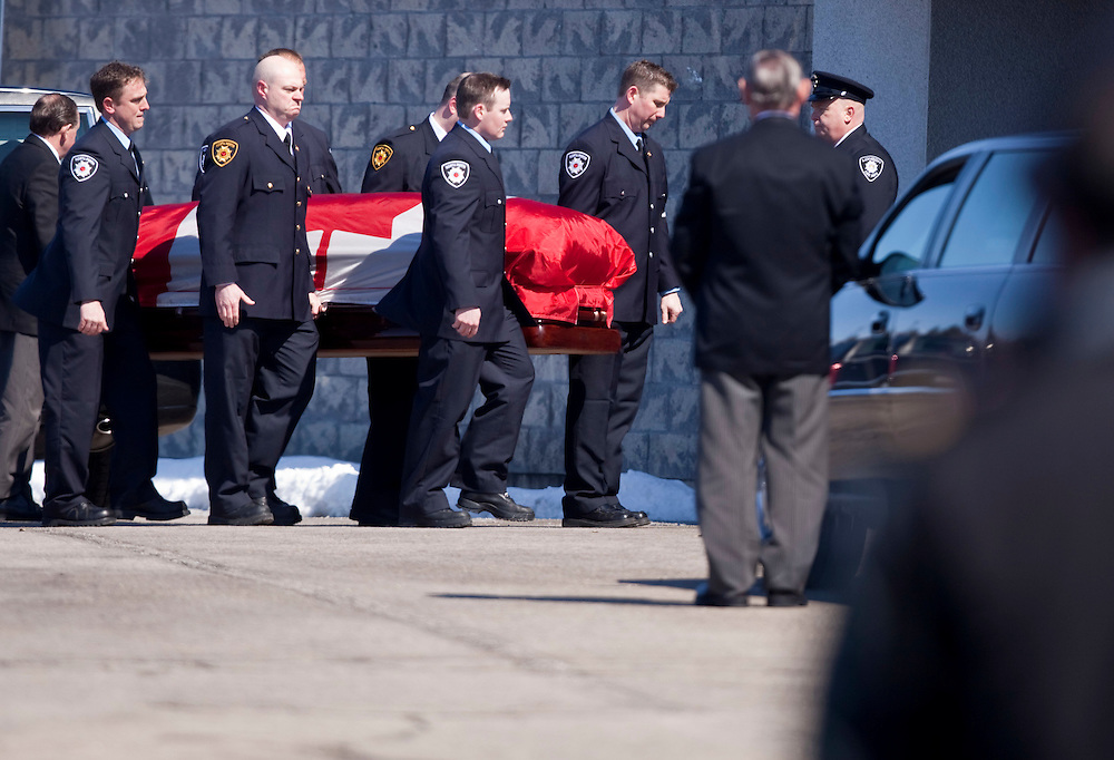 Fire fighters carry the casket of fallen  firefighter Kenneth Rae during a funeral procession in Listowel Ontario, for Rae and fellow fire fighter Raymond Walter Thursday, March 24, 2011. The men were killed fighting a blaze in a dollar store last Thursday when the roof collapsed.<br /> THE CANADIAN PRESS/ Geoff Robins