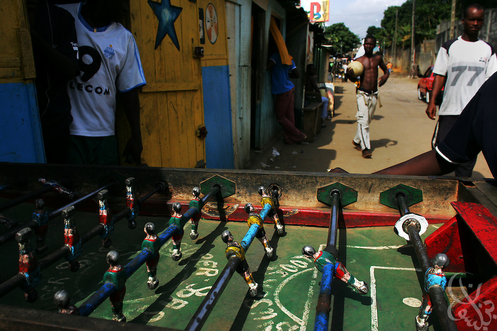 Ivorians pass a streetside fussball table in the Adjame neighborhood of Abidjan, Côte d'Ivoire February 17,2006. Football is an integral part of the social fabric that makes up Ivorian society.