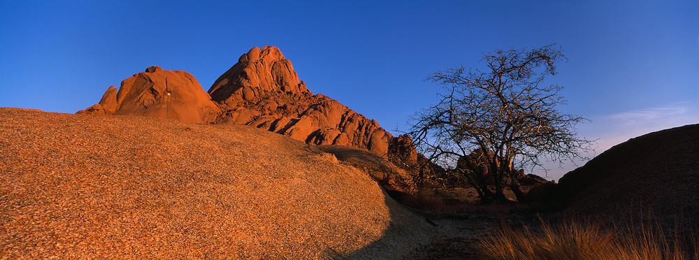 Africa, Namibia, Usakos, Morning sun lights granite rock formations surrounding Spitzkoppe mountain in Namib Desert