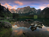 """An after sunset view of the upper lake of Fusine Valromana next to Tarvisio in Friuli, Italy, with Mount Mangart in the background. I had noticed that the clouds were swirling in the wind, so I opted for a very long exposure in order to record the motion. This is stitched from four vertical takes of 90"""" @ f11 each."""