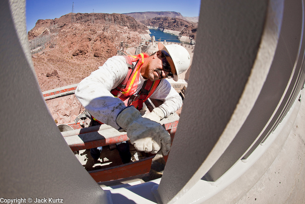 19 AUGUST 2010 --  HOOVER DAM, AZ: Arturo Caro, from Obayashi, works on the Hoover Dam bridge.  Construction work is continuing on the Hoover Dam bypass bridge. The Colorado River Bridge is the central portion of the Hoover Dam Bypass Project. Construction on the nearly 2,000 foot long bridge began in late January 2005 and the completion of the entire Hoover Dam Bypass Project is expected in late 2010.  When completed, this signature bridge will span the Black Canyon (about 1,500 feet south of the Hoover Dam), connecting the Arizona and Nevada Approach highways nearly 900-feet above the Colorado River.  PHOTO BY JACK KURTZ