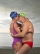 Elderly couple kissing on the beach<br />