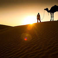 Watching the sunset on a camel safari in the desert of Rajhastan, India