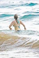 Woman watching the oncoming waves on Maluaka beach in southern Maui, Hawaii