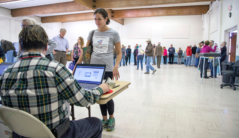 em050217a/a/David Chapman, left, gets Ariana Feinberg her ballot so she can vote in the sugar tax election at St. John's United Methodist Church in Santa Fe, Tuesday May 2, 2017. The line of people waiting to vote went around the room and out the door. (Eddie Moore/Albuquerque Journal