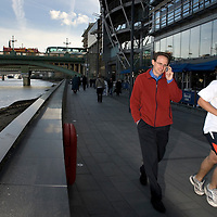 UK. London. Commuters in front of London's Bankside developments between Southwark Bridge and The Tate Modern..