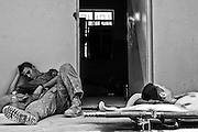 AL FALLUJAH, Iraq - One Marine with F Company, 2d Battalion, 6th Marines, Regimental Combat Team 6 rests against some sand bags while another Marine sleeps on an unused stretcher at the new Iraqi Police Station on June 1st, 2007. The Marines and Iraqi Army are assisting the Iraqi Police in creating the new 10th Precinct Police Station during Operation Alljah in Al Fallujah, Iraq. Regimental Combat Team 6 is deployed with Multi National Forces-West in support of Operation Iraqi Freedom in the Al Anbar Province of Iraq to develop Iraqi Security Forces, facilitate the development of official rule of law through democratic reforms, and continue the development of a market based economy centered on Iraqi reconstruction. (Official USMC photograph by Cpl. Samuel D. Corum)
