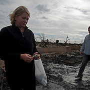 Lauren Mullaney with her husband Patrick Mullaney at right, holds a burned page of her 4-year-old daughter's Winnie the Poo book in front of their home which has been reduced to ash. Breezy Point, Queens. Jonah Markowitz/Falcon Photo Agency