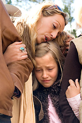 NEWS&GUIDE PHOTO / PRICE CHAMBERS.Cameron Garnick's daughters Jessica, top, and Cheyenne, bottom, console each other during their father's funeral on Tuesday at the Triangle C Ranch near Dubois. The family sang songs and told stories about a man who embodied the western spirit while remaining involved with art and theater throughout his life.
