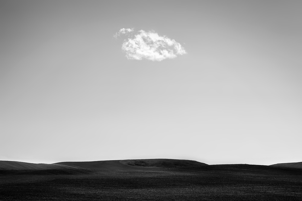 A lost cloud floats over prairie hills East of Calgary.