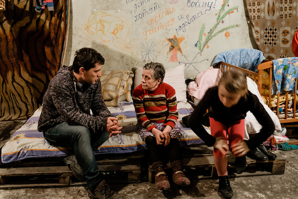 """12 of April 2015 / Petrovski/ Donestk Oblast/ Ukraine - Tomas Vlach, emergency coordinator of the NGO """"People in Need"""" in discussion with Babushka, grandmother of Natacha (on the right), trying to have a better understanding of her family needs."""