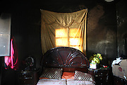 Still life in black. The room walls still coated by black grime from a raging fire inside the house the sleeping room is already furnitured to continue a normal life. Deir Sunbul (contested Jabal Al-Zawiha area) was beeing attacked by syrian army in April, leaving several people dead. Many houses were set on fire by Assad loyalists and inhabitants fled the region fearing new attacks.