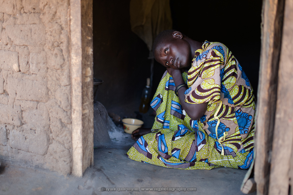 Regina Iyom in the doorway of her home in Imurok Payam in Eastern Equatoria, South Sudan on 9 August 2014. Regina's husband is a government soldier, and has been away for about a year. Having come to her current home after having had to flee fighting in Juba in December 2013, she says she receives no support from him—locals say that soldiers frequently go unpaid for long periods of time. Facing acute food insecurity, Regina received seed to plant from Plan International. (On the day she was pictured, Regina was very unwell, with malaria, she said.)