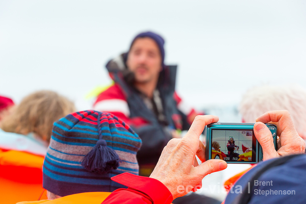 A local guide talks about ice, glaciers and the Vatnajokull ice cap whilst a tourist takes a photo with a point and shoot camera. Jokulsarlon, edge of Vatnajokull National Park, Iceland. July.