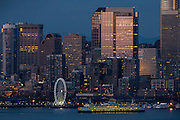 A ferry passes by Seattle's Great Wheel on the downtown waterfront. (Dean Rutz / The Seattle Times)