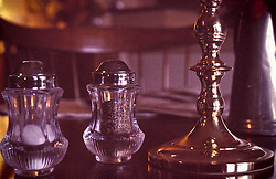 Close up glass salt pepper shakers brass candle stick formal dining room table top