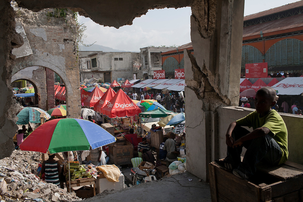 A boy sits inside a destroyed building on Grand Rue on July 9, 2010 in Port-au-Prince, Haiti.