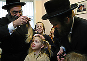 In Stamford Hill, London, United Kingdom on the 3rd birthday of a Orthodox Jewish boy he has his first ever hair cut leaving his peyos (sideburns) to grow. Here his Grandfather cuts the main part of his hair away watched closely by the boy, his father and family. He will now begin to learn the Torah.