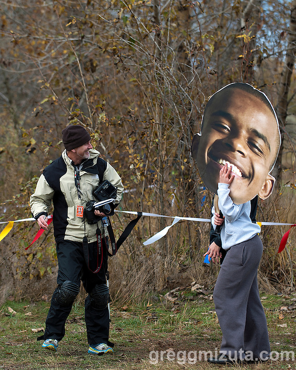 Idaho Statesman photojournalist Kyle Green and Alexis Dilworth holding a large cutout of the face of Mountain View runner Adrian Jones during the Idaho High School Cross Country State Championships, November 1, 2014 at Eagle Island State Park, Eagle, Idaho.