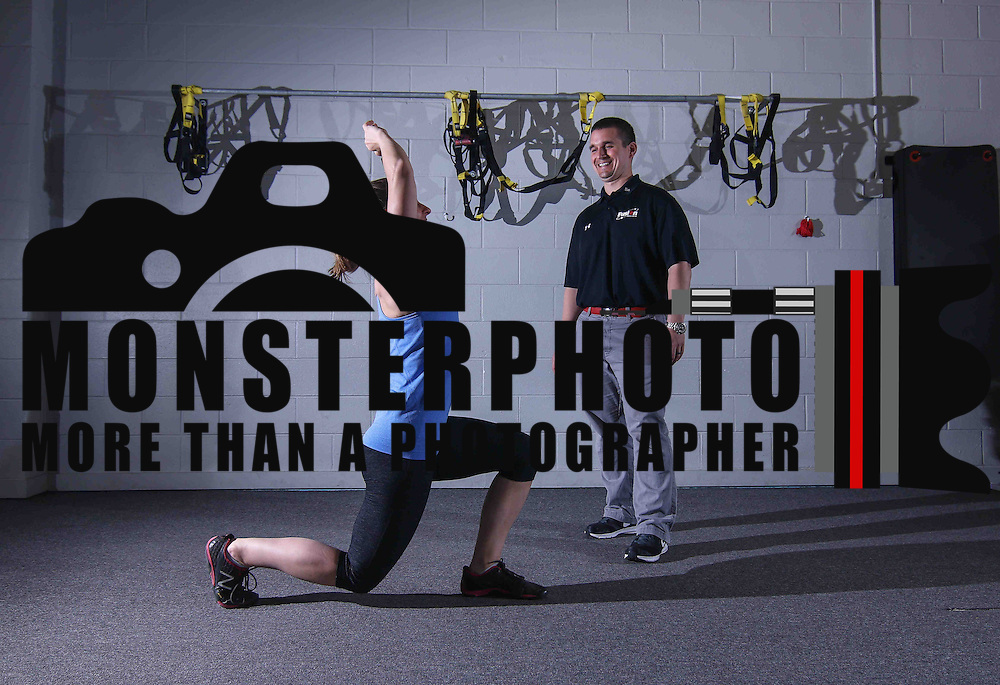 Owner Nic DeCaire, RIGHT, and Head Coach Leigh Anne Emrich of Fusion Fitness demonstrates a reverse lunges  techniques Thursday, April 23, 2015 at Fusion Fitness in Newark Delaware.