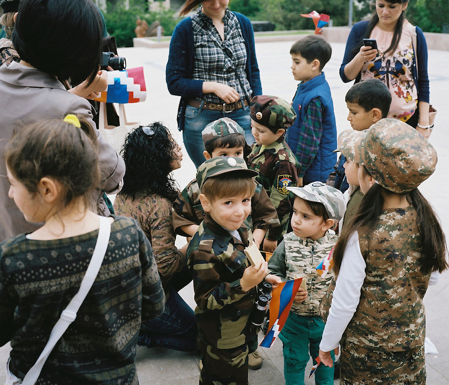 Children dressed in military costume and carrying flags pose for a picture together following a ceremony commemorating both the victory over Nazi Germany in the Second World War as well as the fall of the strategic town of Shushi to Armenian forces on Monday, May 9, 2016 in Stepanakert, Nagorno-Karabakh.