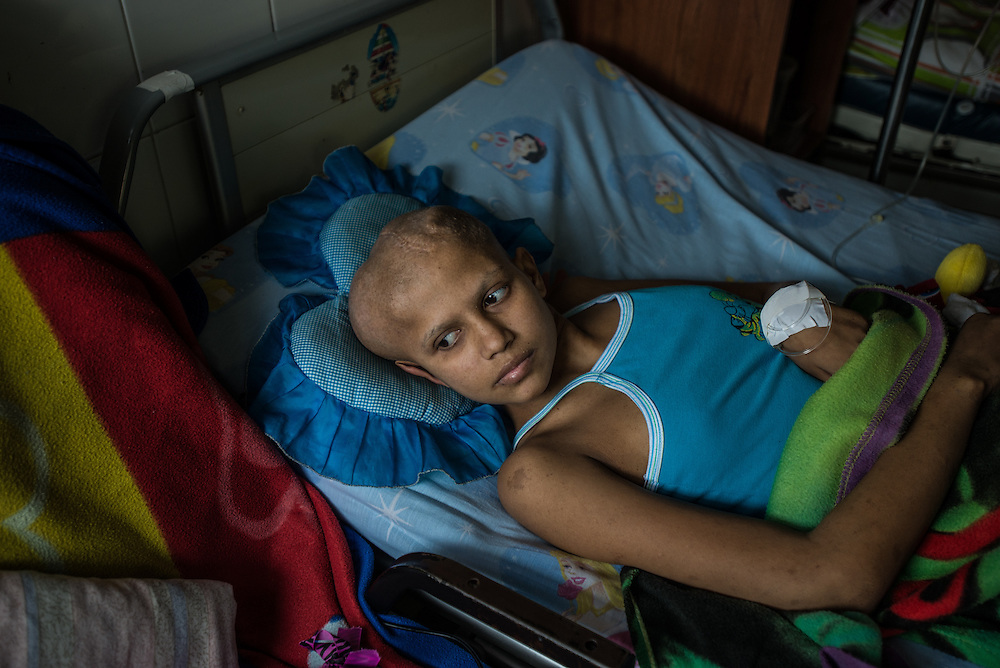 PUERTO LA CRUZ, VENEZUELA - APRIL 15, 2016: Fifteen-year-old Yulitza Roa has a large brain tumor, and has been in the hospital for over a year, unable to walk because of the tumor. She has had three surgeries so far, but needs another to remove the tumor. Doctors have not been able to operate yet, because she needs a CAT scan of her brain, that the hospital isn't equipped to do. Doctors also told her and her family that they must provide two packages of neuro patties, absorbant material needed during the surgery, that cost 10,000 VEF each package. Yulitza's family does not have the financial resources to pay for the private CAT scan, nor the neuro patties, so Yulitza has to keep waiting for her surgery, while her family looks for donations to pay for the things that were previously provided for free from the state before the hospital crisis. Hospital Universitario Dr. Luís Razetti is one of the worst state-run, public hospitals in Venezuela. Doctors compare it to working in a war zone - they regularly have to turn patients away, because they don't have the majority of medicines or medical equipment and supplies needed to give them medical attention. When they do accept patients, they have to work with extremely limited resources, because they don't have the supplies they need for things like X-Rays, and many exams nd operations. The hospital's infrastructure is crumbling, and staff don't have all the cleaning supplies required to keep the hospital sanitary. The hospital also suffers from weekly shortages of running water and electricity. Despite having the largest oil reserves in the world, falling oil prices and wide-spread government corruption have pushed Venezuela into an economic crisis, with the highest inflation in the world and chronic shortages of food and medical supplies. PHOTO: Meridith Kohut