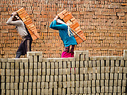 09 MARCH 2017 - BAGMATI, NEPAL: Workers carry finished bricks to storage area at a brick factory in Bagmati, near Bhaktapur. There are almost 50 brick factories in the valley near Bagmati. The brick makers are very busy making bricks for the reconstruction of Kathmandu, Bhaktapur and other cities in the Kathmandu valley that were badly damaged by the 2015 Nepal Earthquake. The brick factories have been in the Bagmati area for centuries because the local clay is a popular raw material for the bricks. Most of the workers in the brick factories are migrant workers from southern Nepal.           PHOTO BY JACK KURTZ