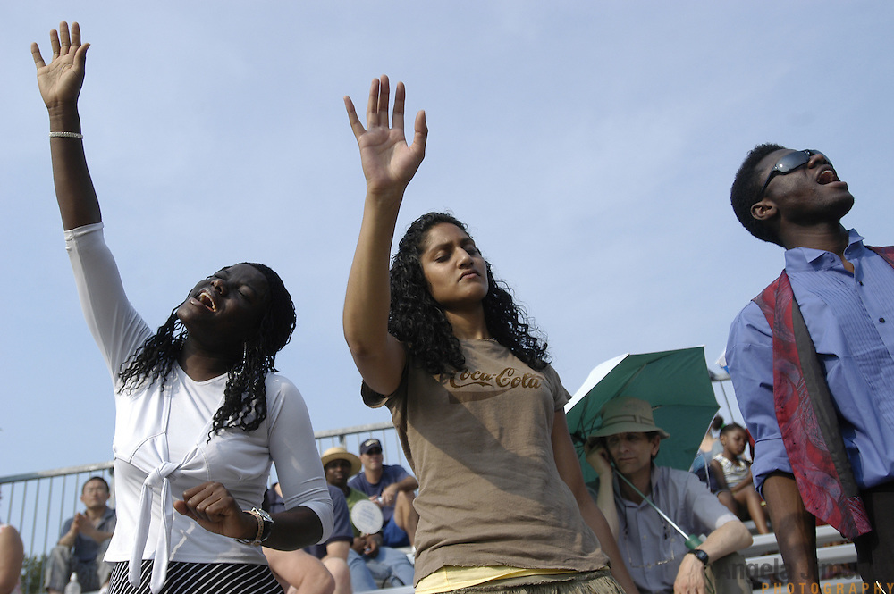 Damaris Yamoah, 30, from left, Amanda Jaundoo, 24, and Kosj Yamoah, 25, all members of the Glad Tidings Tabernacle Church in Manhattan, sing during the last day of the Greater New York Billy Graham Crusade at Flushing Meadows Corona Park in Queens, New York City on June 26, 2005. The three day event was organized by the Billy Graham Evangelistic Association.