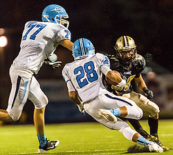 Corona Del Mar Sea Kings Anthony Battista (28) runs while Ian Redman (77) blocks Dayton Weems (36) of Laguna Hills Hawks.