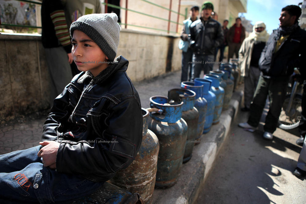 A boy sit on a gas bottle in line in Idlib to wait for a gas supply. Many towns in are suffer by a lack of available fuels. Idlib, Province of Idlib, Syria.