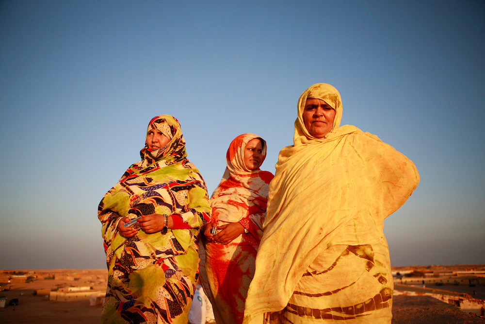 """Western Sahara, a Territory on the north-west coast of Africa bordered by Morocco, Mauritania and Algeria, was administered by Spain until 1976. Both Morocco and Mauritania affirmed their claim to the territory, a claim opposed by the Frente Popular para la Liberación de Saguia el-Hamra y de Río de Oro (Frente POLISARIO). The Sahrawi refugee camps in Tindouf, Algeria, are a collection of refugee camps, set up in the Tindouf Province, Algeria in 1975-76 for Sahrawi refugees during the period of war. The camps are divided into four wilayas (districts) named after towns in Western Sahara; Laayoune, Awserd, Smara and Dakhla. In addition comes the smaller satellite camp """"February 27"""", surrounding the boarding school for women, and the administrative camp Rabouni. See here are a group of women at the end of the day in Camp """" February 27"""" watching sunset from one of the hills. Photo by UNMIT/Martine Perret. June 2010"""