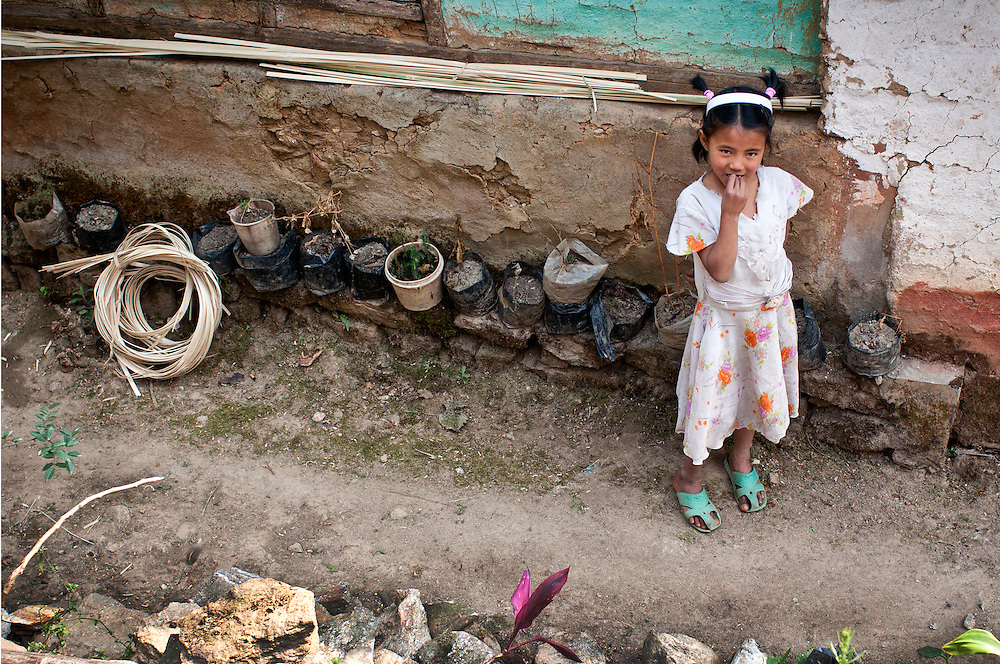 A young girl looking coy amid dirt and rubbish.