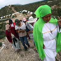 Followers of Nino Fidencio, a curandero or healer who passed away in the 1938, walk to healing session on top of a hill just outside in Espinazo, Mexico on Thursday, October 19, 2006. Followers of Nino Fidencio believe that his spirit can posses other healers, who once possessed, speak in child-like voices and perform a variety of medical cures on their followers.  His believers, an estimated 20,000, gather in his hometown for a three-day festival twice a year in March and October. (Photo/Scott Dalton)