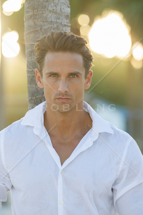 sexy man in a white shirt at sunset on the beach in Miami, FL