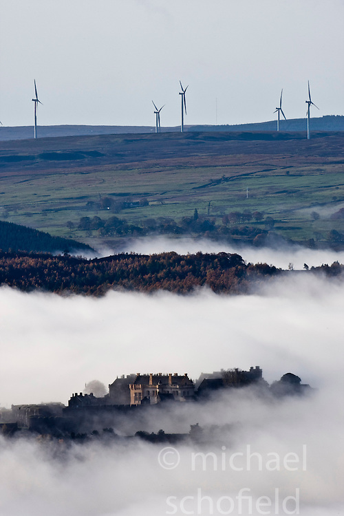 Stirling Castle seen through morning mist. The castle stands on the summit of Castle Hill and is one of the largest and most important castles, both historically and architecturally, in Scotland. At the top can be seen the turbines for the Earlsburn wind farm..Pic ©2010 Michael Schofield. All Rights Reserved.